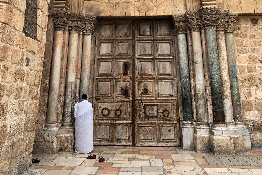 A worshiper prays outside the Church of the Holy Sepulchre, the traditional site of Jesus' tomb. Its wooden doors are shut now to deter the spread of COVID-19, and only clergy may perform the daily prayer rituals inside.