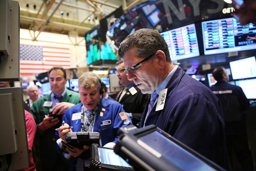 Traders work on the floor of the New York Stock Exchange after the morning bell on May 1.