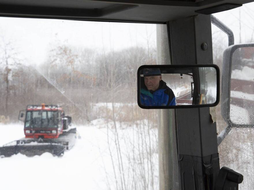 While sitting in a tractor, volunteer Don Olson waits for Lucas Olen to finish grooming a trail on Tuesday at the Vasaloppet Nordic Ski Center in Mora, Minn. Olson says a spreader holds about 15 cubic yards of snow, which will cover about 10 meters.