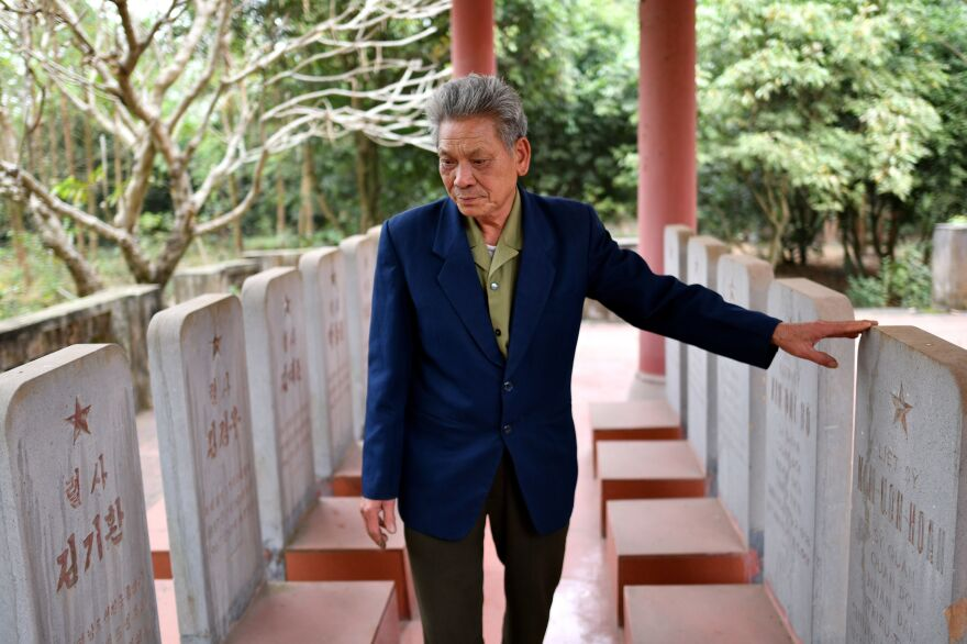 At a war memorial in Bac Giang province, Duong Van Dau views the tombstones of North Korean pilots killed during the Vietnam War. Headstones are etched with the names of the dead in Korean on one side, and Vietnamese on the other.