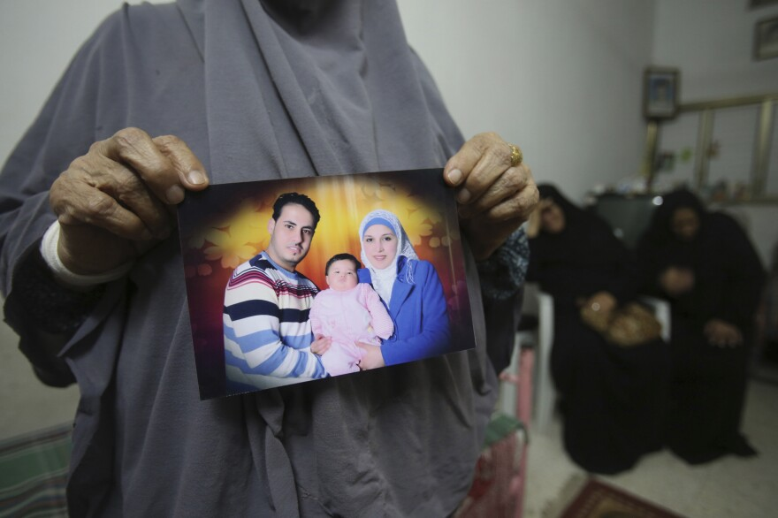 The mother of Shukri al-Assoli holds a picture of him with his wife and daughter, after the boat carrying them was rammed and capsized.