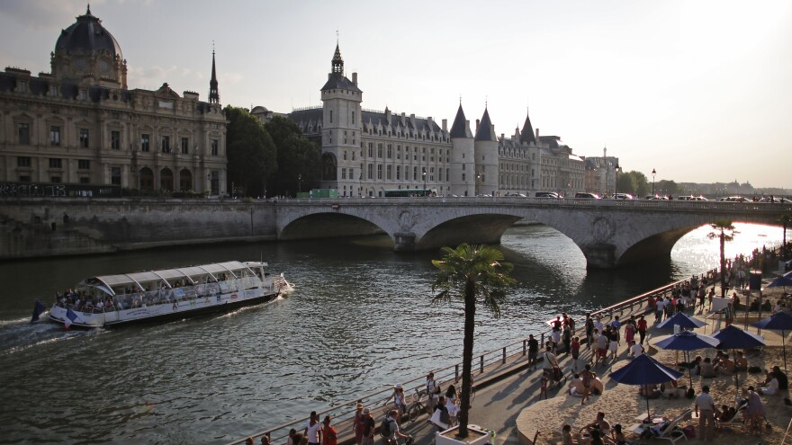 """People enjoy the sun next to Pont Neuf bridge as """"Paris Plage, or Paris Beach, opens along the banks of the Seine river in Paris, on July 20. The annual free event brings a half-mile of beach into the heart of the French capital."""