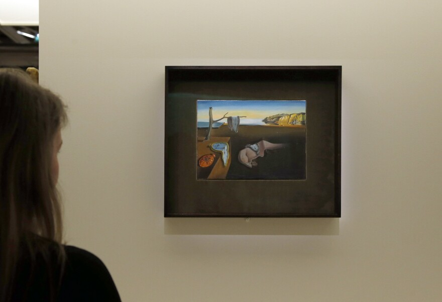 A visitor looks at Dalí's <em>The Persistence of Memory</em> at an exhibition in Paris in 2012.