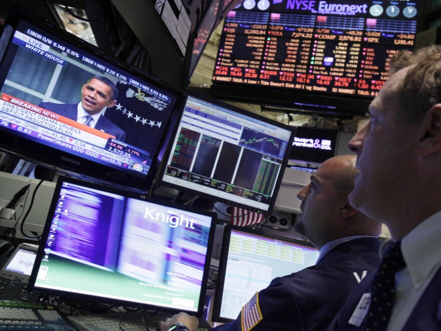 Specialists on the floor of the New York Stock Exchange watch President Obama's televised speech on debt reduction Monday. Obama wants to require investment fund managers to pay at least the same percentage in taxes as middle-income Americans.