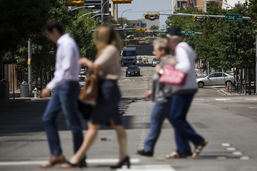 Pedestrians cross Colorado Street in downtown Austin.