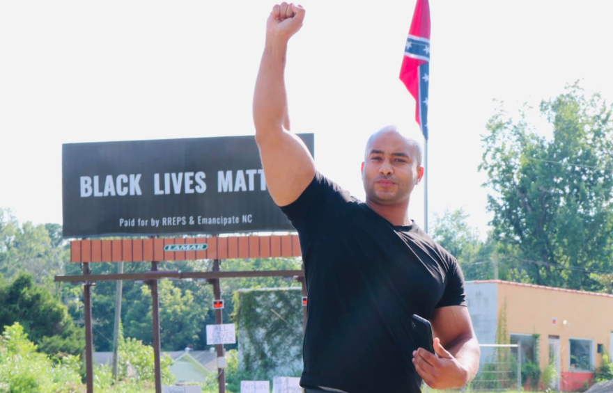 Social justice activist Kerwin Pittman stands in front of the new Black Lives Matter billboard in Pittsboro.