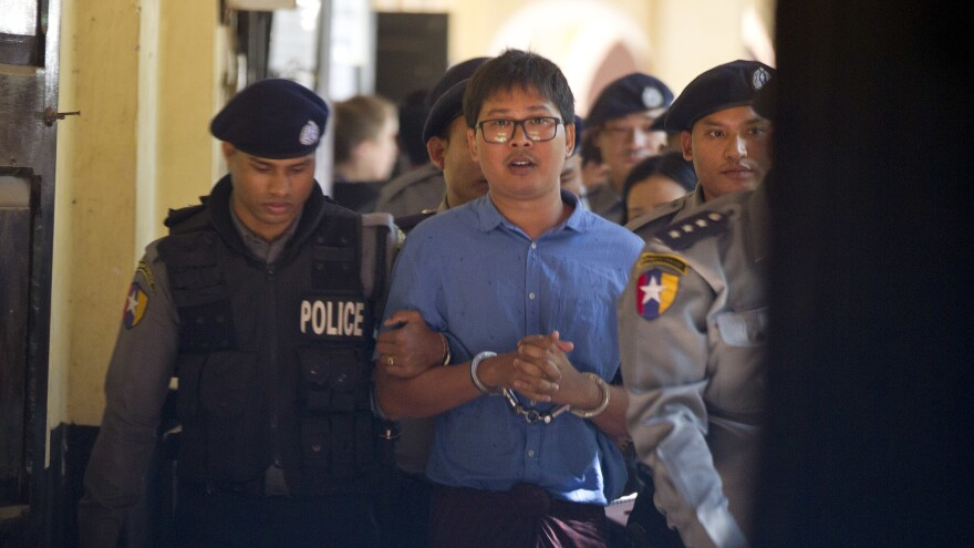 Reuters journalist Wa Lone is escorted by police as he leaves court Wednesday outside Yangon, Myanmar. He and U Kyaw Soe Oo, who had been investigating a possible mass grave in Rakhine state, stand accused of violating the Official Secrets Act and face up to 14 years in prison.
