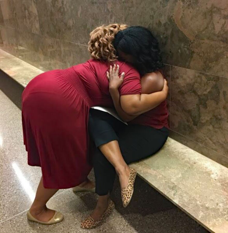 Waiting outside a courtroom for their eviction cases to be heard, Nikeia Diaz, left, and Pat, strangers until today, offer support to each other.