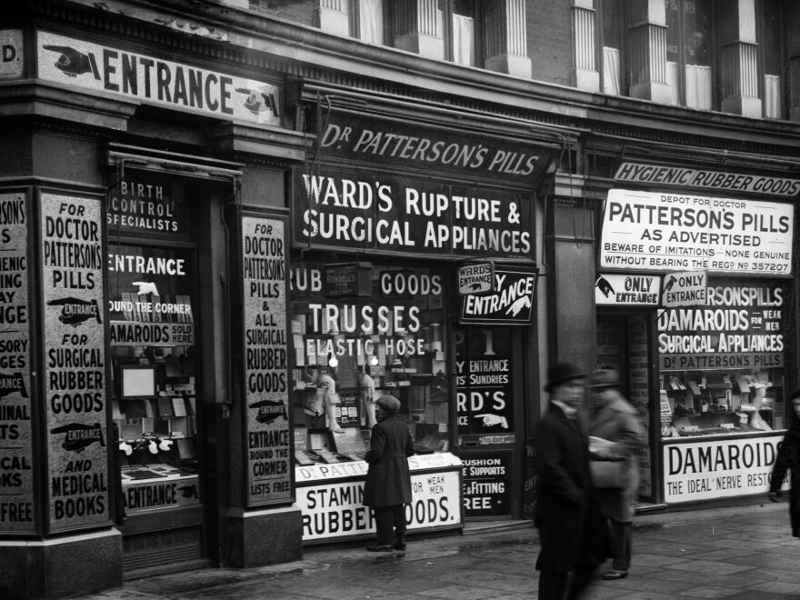 Ads for patent medicines and medical appliances dominate a 1930s storefront in England.