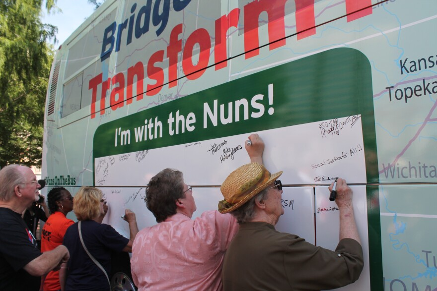 Rally attendees sign the nuns' bus as an oath of their commitment to social justice causes.