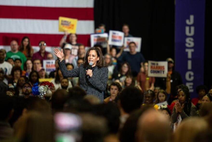 Sen. Kamala Harris speaking with microphone at a campaign event surrounded by a crowd.