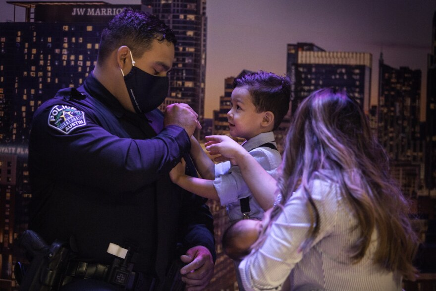 Officer Thomas Bores gets help from his son pinning a police badge on his shirt.