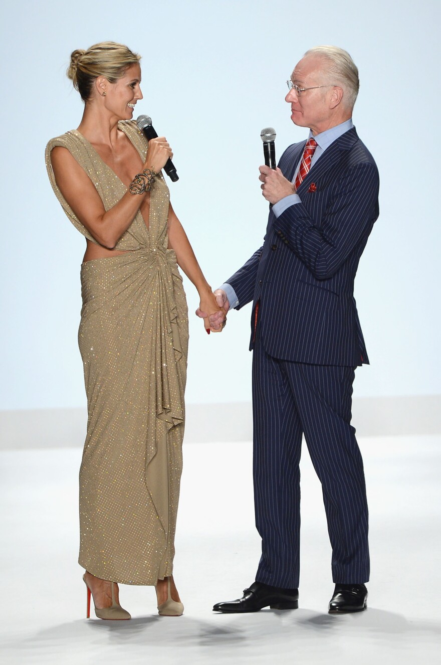 Heidi Klum and Tim Gunn walk the runway at the <em>Project Runway</em> spring 2013 fashion show in New York City in September 2012.