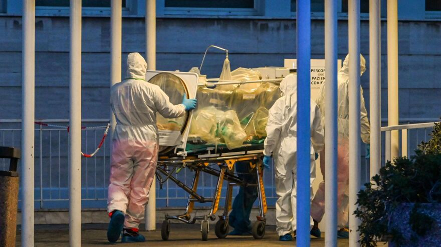 Medical workers transport a patient into a newly built temporary hospital on March 16 in Rome. Doctors in Italy are making difficult decisions about who should receive care.