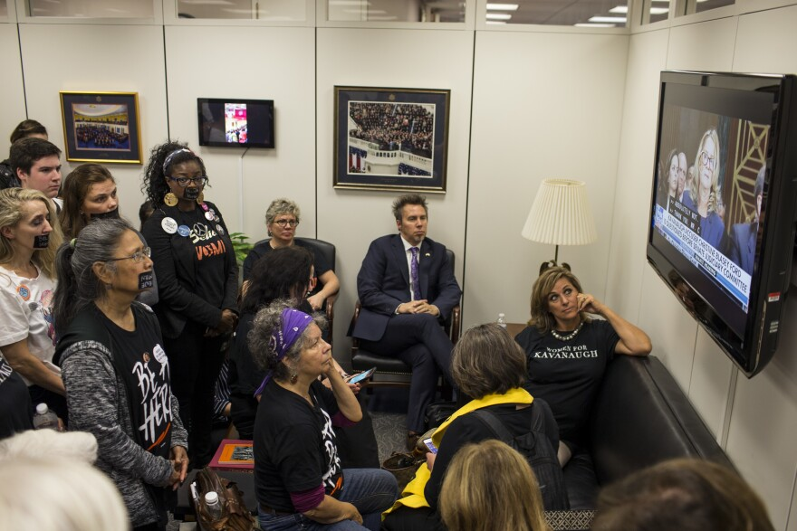 Protesters and supporters of Brett Kavanaugh's nomination watch Christine Blasey Ford's testimony from Sen. Chuck Grassley's office in Washington, D.C.