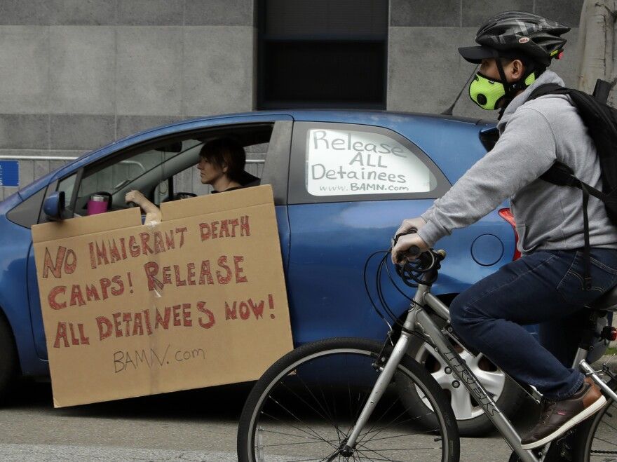 A masked cyclist passes a motorist protesting in a vehicle at a U.S. Immigration and Customs Enforcement field office last month in San Francisco.