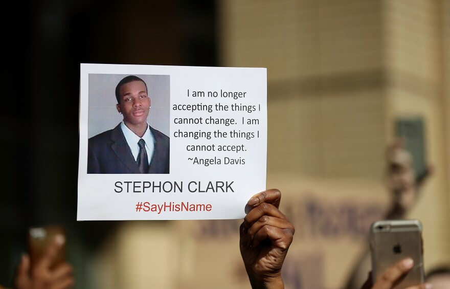 A protester holds a photo of Stephon Clark during a Black Lives Matter protest in Sacramento on March 22, 2018.