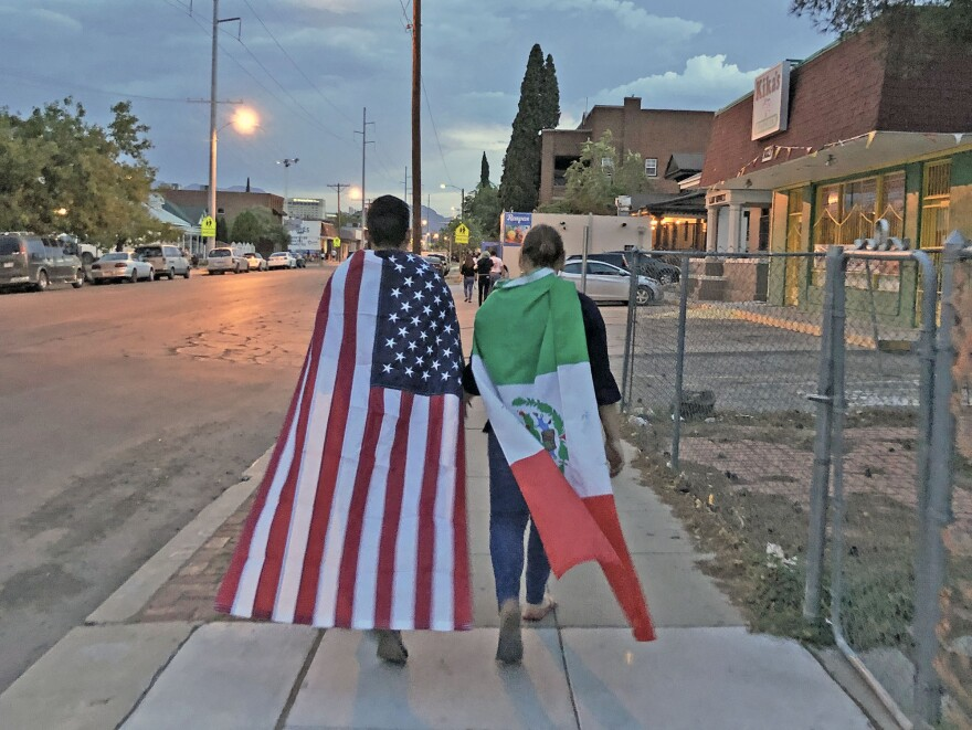 A couple draped in U.S. and Mexican flags leave after the mural unveiling ceremony in El Paso.
