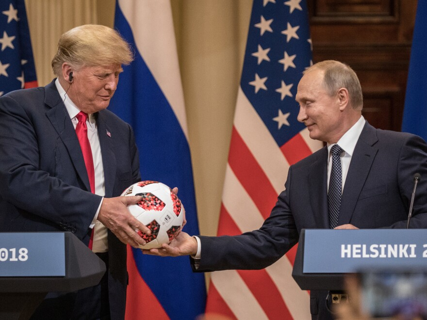 Russian President Vladimir Putin hands President Trump a World Cup soccer ball during a joint news conference after their summit on July 16, 2018, in Helsinki.