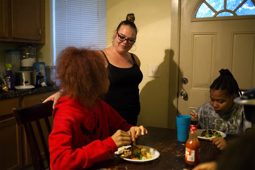 Regina Hartfield speaks with her daughters Khia, 14, and Destinee, 12 , as they eat dinner. Hartfield's children were dropped from Missouri's Medicaid program.