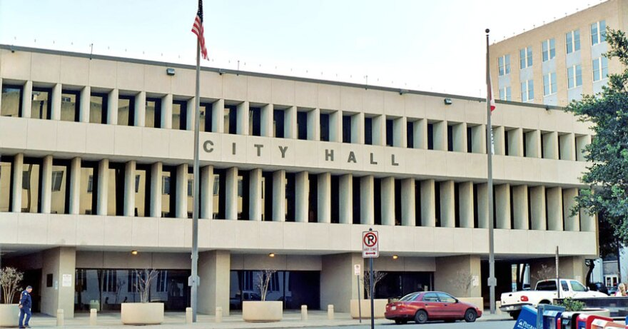 "In this photo, there is a large gray concrete building with the words ""CITY HALL"" on the front."