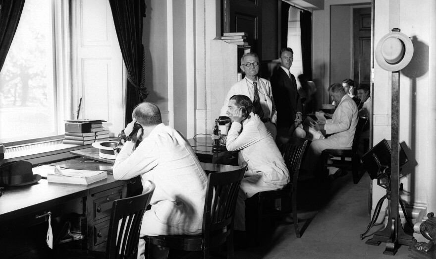 Newspaper reporters who cover President Roosevelt work in the temporary press room at the White House in July 1934.