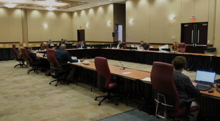 A long, u-shaped table with county commissioners seated around it.
