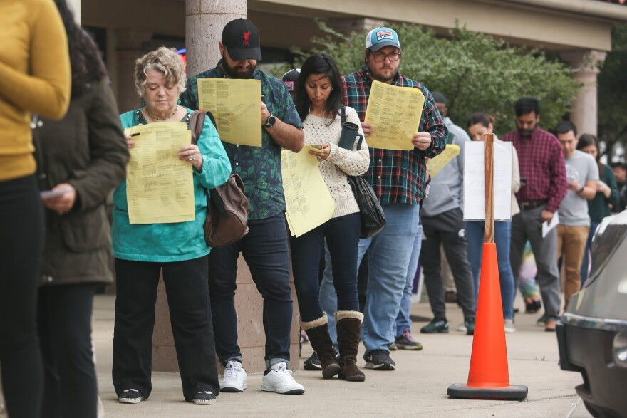 Voters look at sample ballots while waiting to vote at Randalls on Braker Lane on Tuesday.