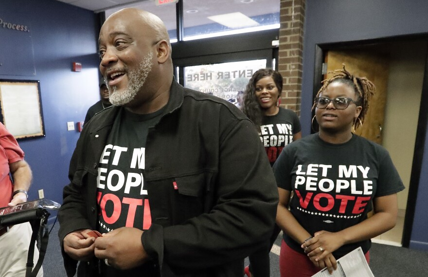 Desmond Meade, president of the Florida Rights Restoration Coalition, arrives with family members at the Supervisor of Elections office in Orlando in January 2019 to register to vote. Meade's group works to restore voting rights to felons.