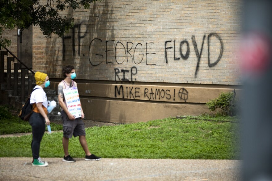 """George Floyd"" and ""RIP Mike Ramos"" graffiti is spray-painted onto the side of Austin Police Department headquarters."