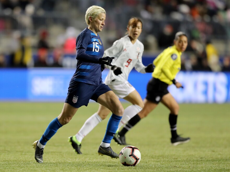 U.S. forward Megan Rapinoe takes the ball as Japan's Hina Sugita stays close on the first day of the SheBelieves Cup in Chester, Penn., on Wednesday night.