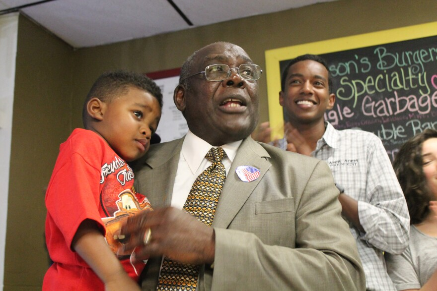 Lee Smith, a candidate in Ferguson's Ward 3, holds his great-grandson Brandon while speaking to supporters at the Ferguson Burger Bar.