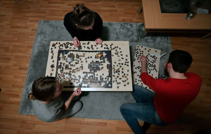 Flat-mates work on a puzzle in their living room in Dortmund, Germany, on March 27, 2020.