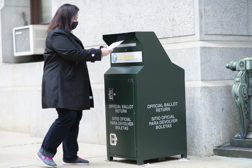 A voter casts her early voting ballot at drop box outside of City Hall on Oct. 17, 2020 in Philadelphia.