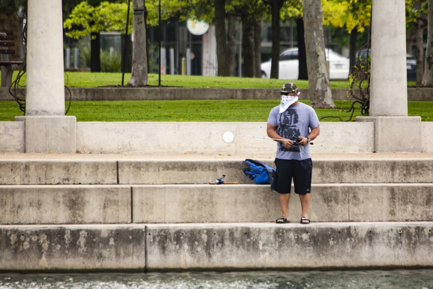 A man wears a bandana over his face while fishing at Mueller Lake Park on March 27.