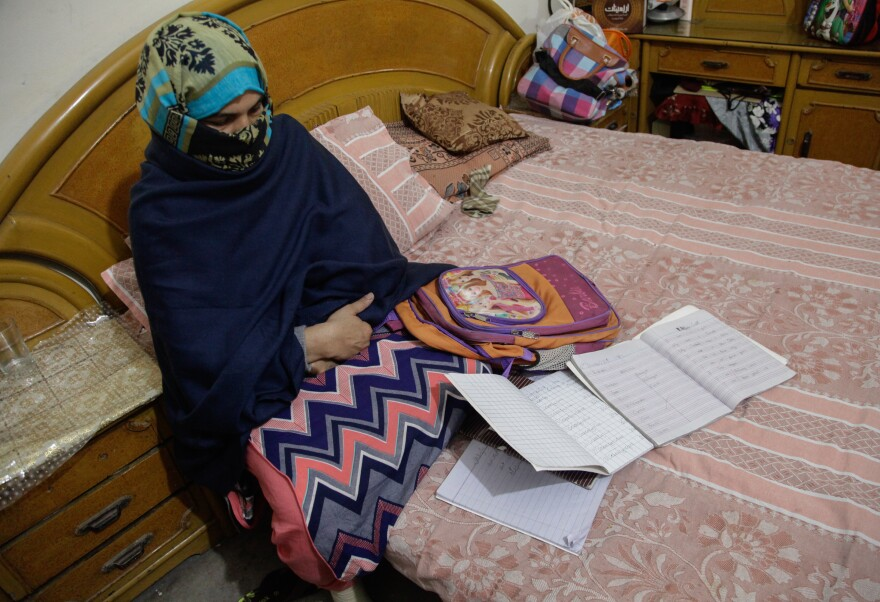 Zainab's mother, Nusrat Amin, sits with her slain daughter's school bag and notebooks.