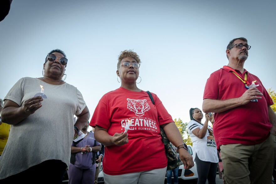 Herzog Elementary School volunteer Marion Reese and teachers Angela Ware and James Kaegel at a vigil at the school for student Jurnee, a third-grader who was shot a few days earlier. Aug. 28, 2019