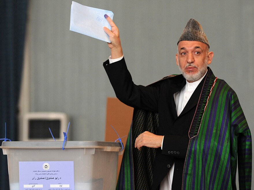 Afghan President Hamid Karzai gestures before casting his vote at a polling station in Kabul, Sept. 18, 2010, in parliamentary elections that were marred by allegations of fraud.