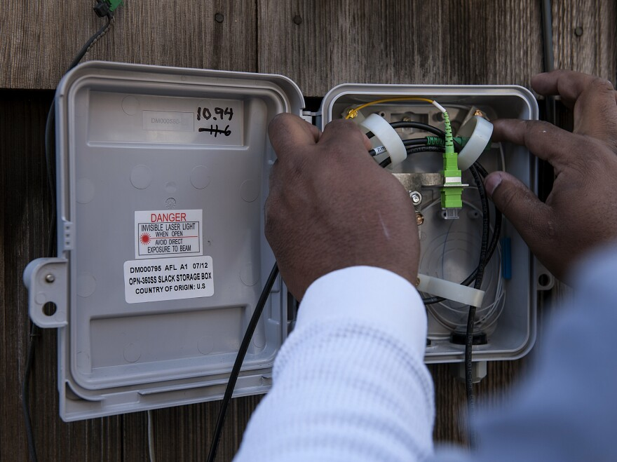 A Google broadband technician installs a fiber-optic network at a home of one of the early Google Fiber customers in Kansas City, Kan., in 2012.