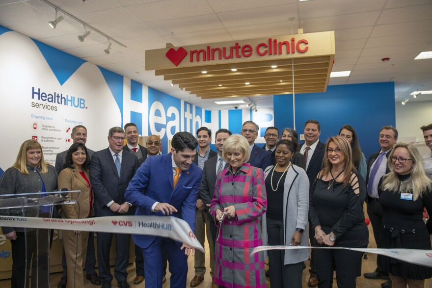 A group of people cut a CVS ribbon to symbolize the opening of the new clinic.