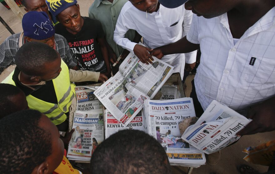 Local residents gather around a newspaper vendor Friday to read articles about the attack in Garissa.