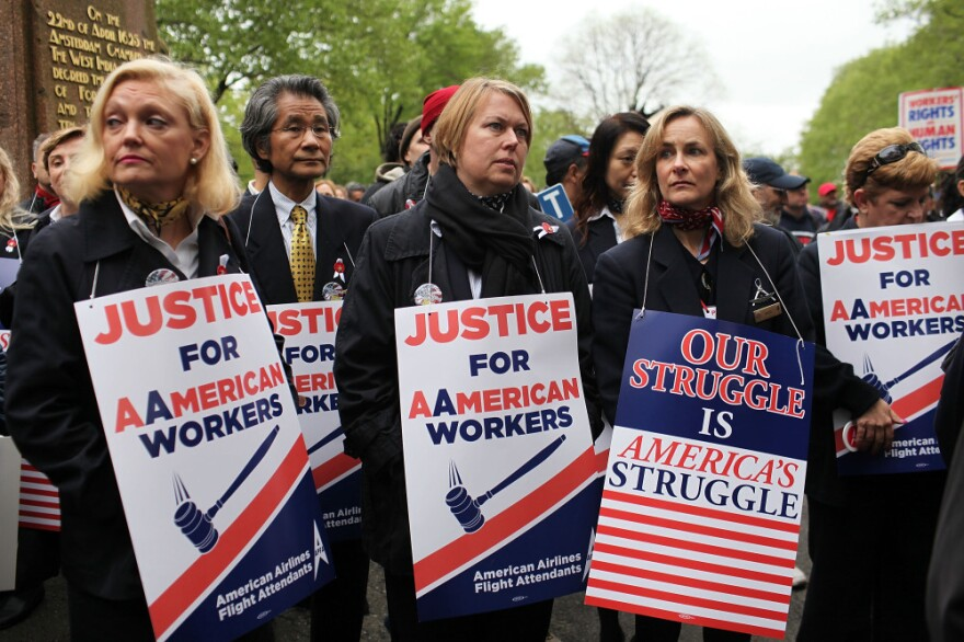 American Airlines and American Eagle employees protest Monday in New York City against American's plans to cut jobs and labor costs while under bankruptcy court protection. American is seeking permission to break up union contracts and cut expenses, but the unions oppose those plans and support a potential takeover bid by US Airways.