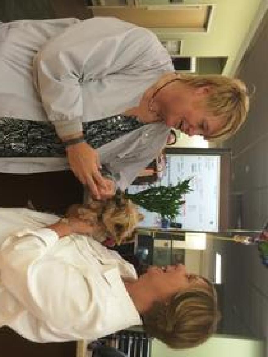Viera Hospital patient advocate Geraldine Stubbert speaks with Monica Burchfield, the daughter of a patient, who brought her Yorkie named Demi to see her father Max Driver.
