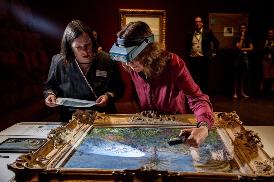 Conservator Felicitas Klein, right, traveled from Germany with<em> Villas at Bordighera,</em> an 1884 painting by Claude Monet. She inspects the painting at the Denver Art Museum, along with senior paintings conservator Pamela Skiles.