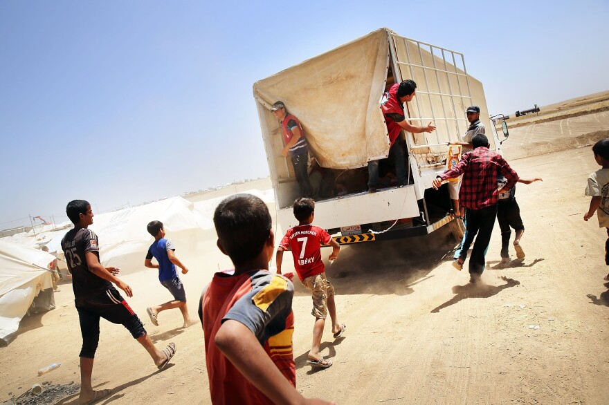 Iraqi boys chase a Red Crescent truck delivering food on Monday in Khazair, Iraq. Khazair, in northern Iraq, is now home to an estimated 1,500 internally displaced persons from the recent fighting.