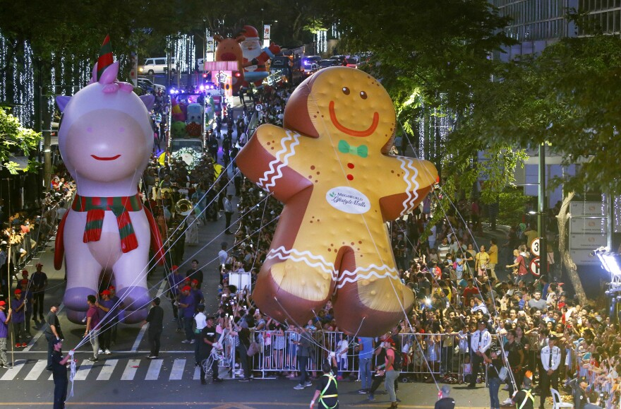 "Hundreds of residents watch as colorful floats and larger-than-life balloons, including the ""Happy Pink Unicorn"" and the ""Giant Ginger Bread,"" are paraded ahead of the Christmas celebration at a shopping area in greater Manila, Philippines, on Dec. 8."