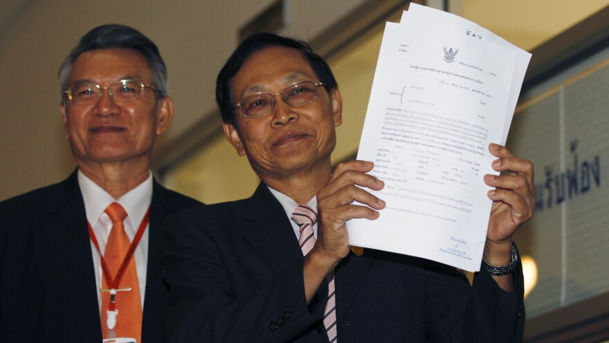 Thailand's Attorney Director General, Department of Special Litigation Chutichai Sakhakorn, right, holds filed charging papers as Director General, Department of Investigation, Surasak Threerattrakul looks on at the Supreme Court in Bangkok Thursday.