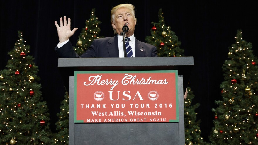 """President-elect Trump, flanked by decorated Christmas trees, speaks at rally in Wisconsin. Trump said at the event, """"We are going to say Merry Christmas again,"""" implying a war on Christmas."""