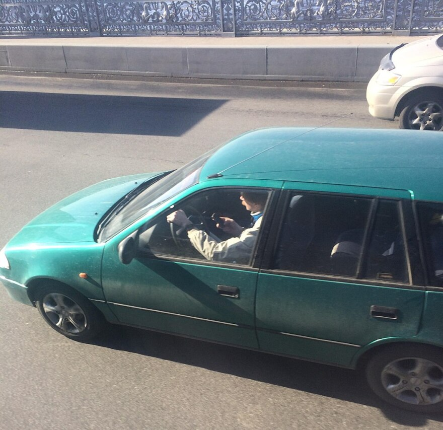 Man in green van texts while he drives over a bridge.