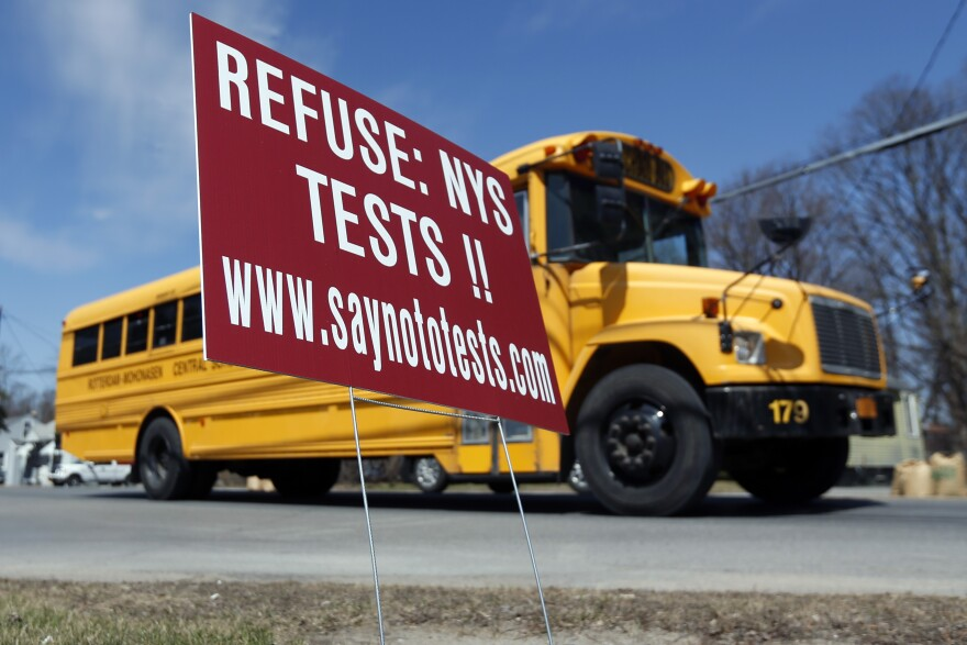 A school bus passes a sign encouraging parents to have their children opt out of state tests in Rotterdam, N.Y.